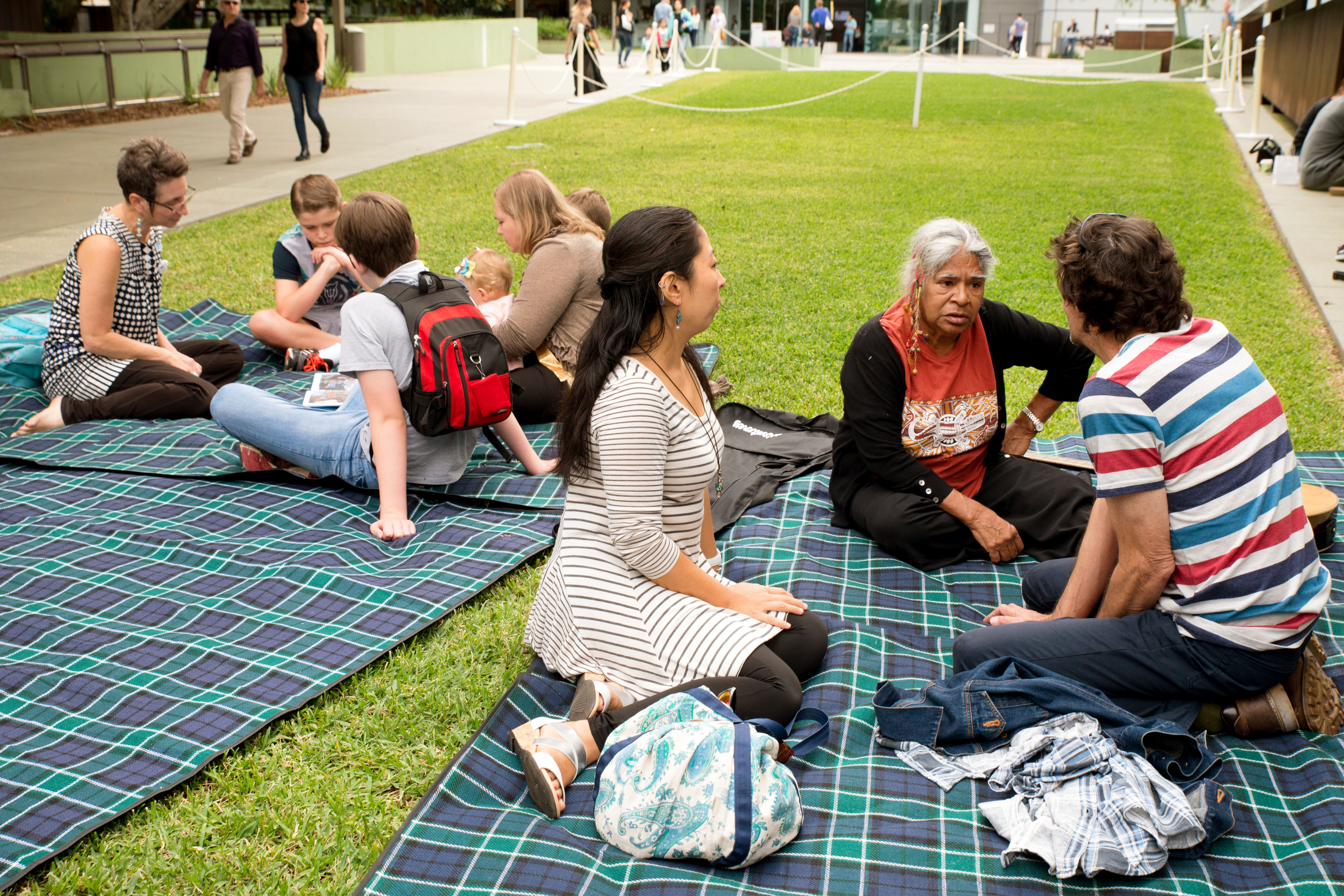 Group  of people sitting on the lawn talking