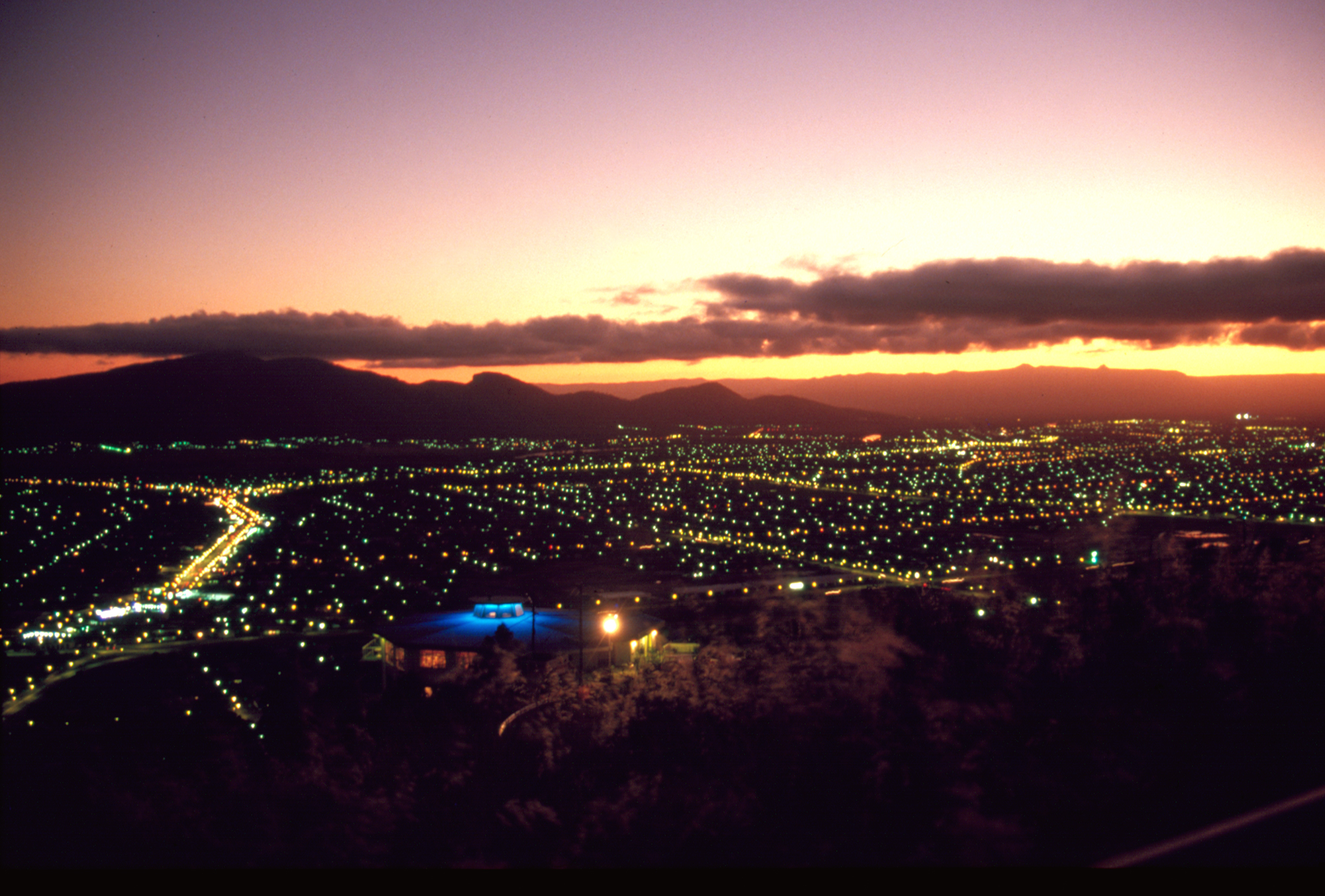 City lights of Townsville twinkle as the sun disappears below the horizon 1985