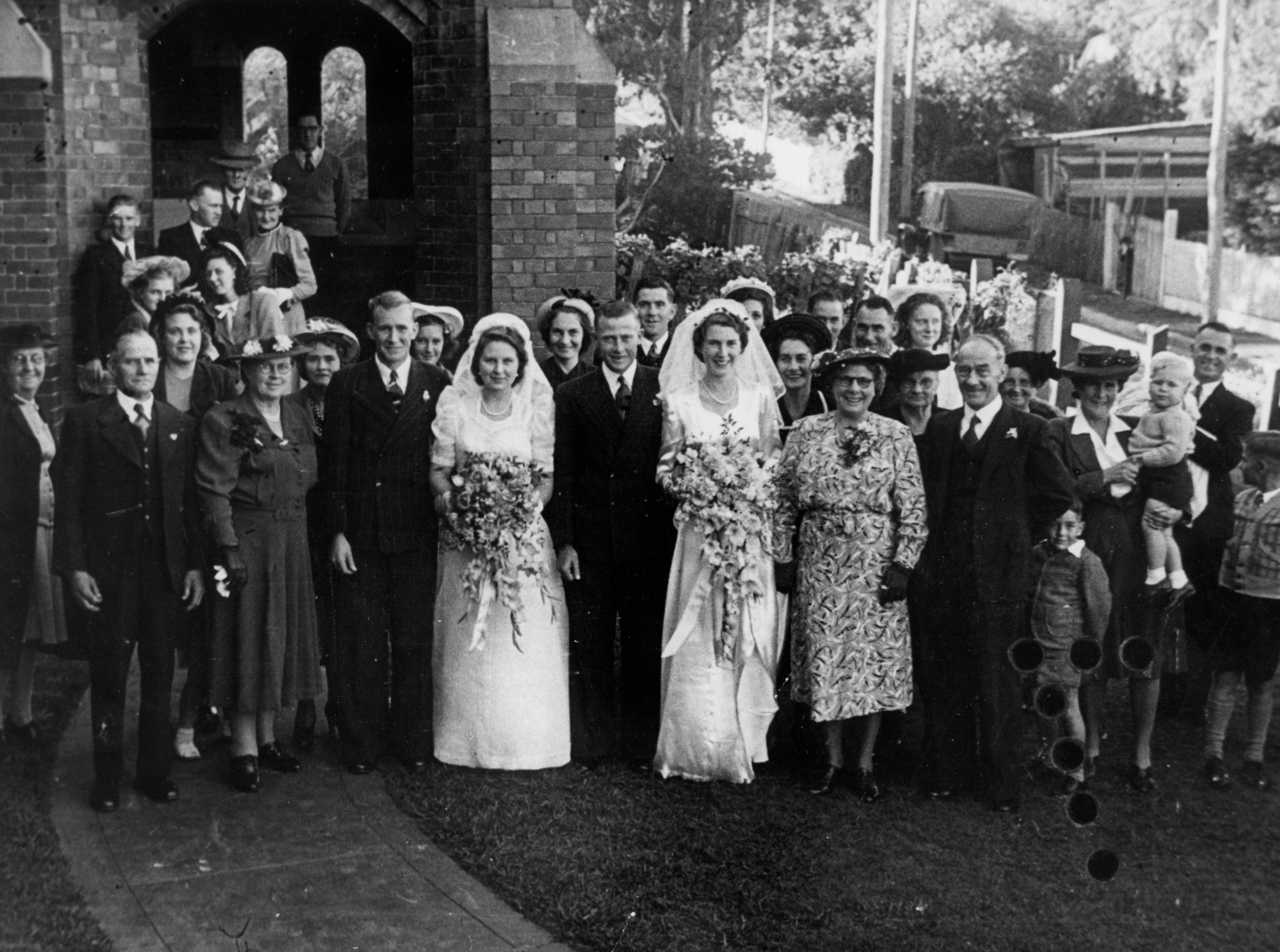 Two brides with large bouquets stand next to their grooms in front of a large group of people oustide a church