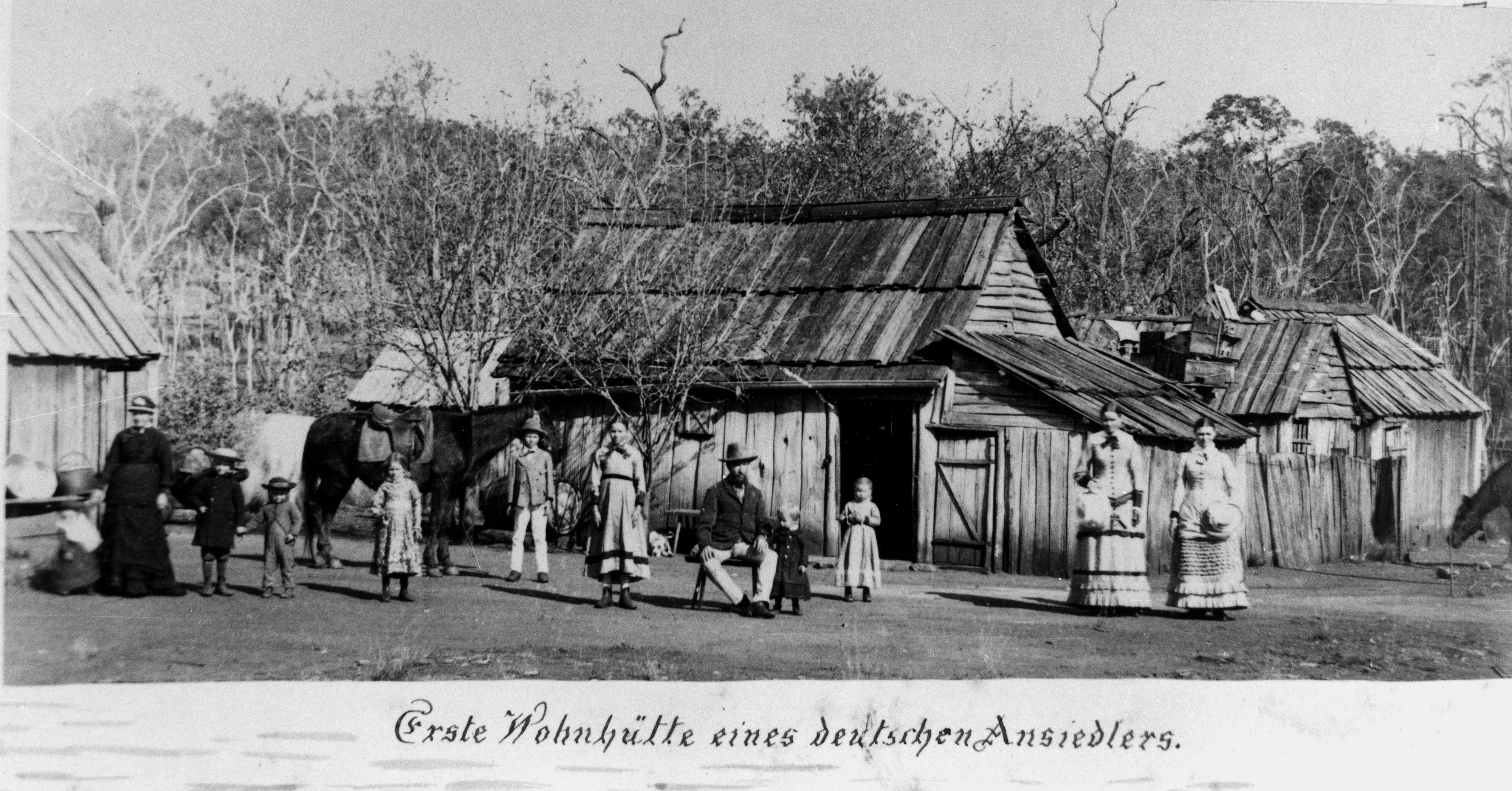 11 people of various ages standing in front of a wooden house and a horse