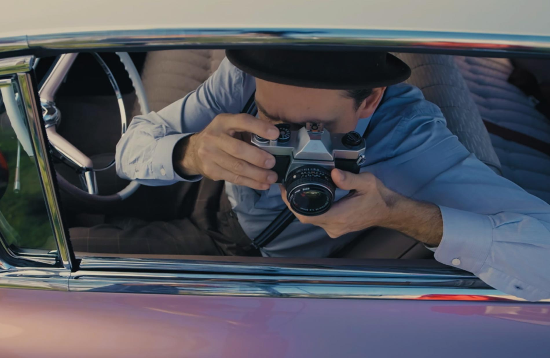 Home exhibition man with camera in a car