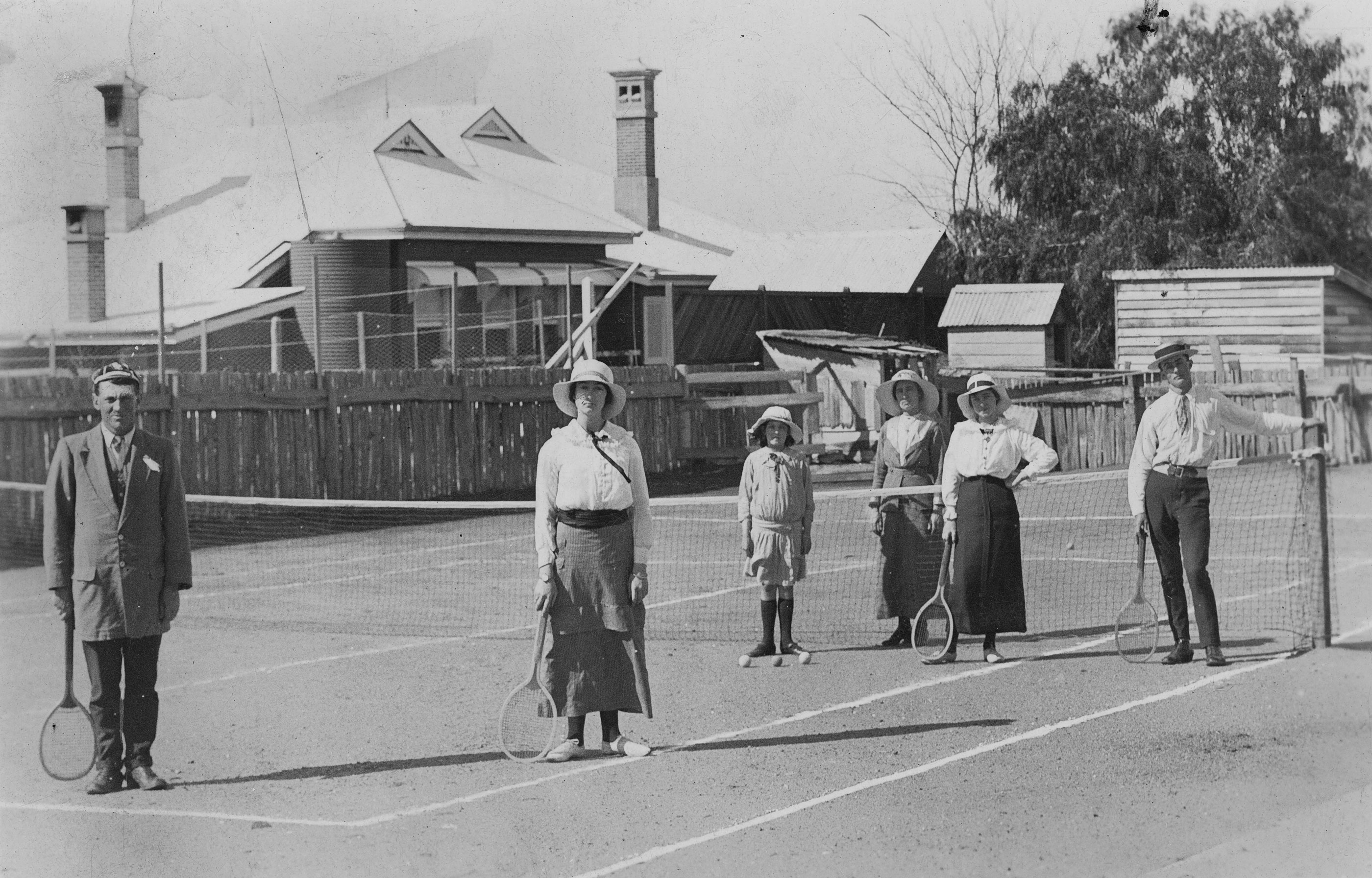 Tennis players standing on a tennis court ca 1915