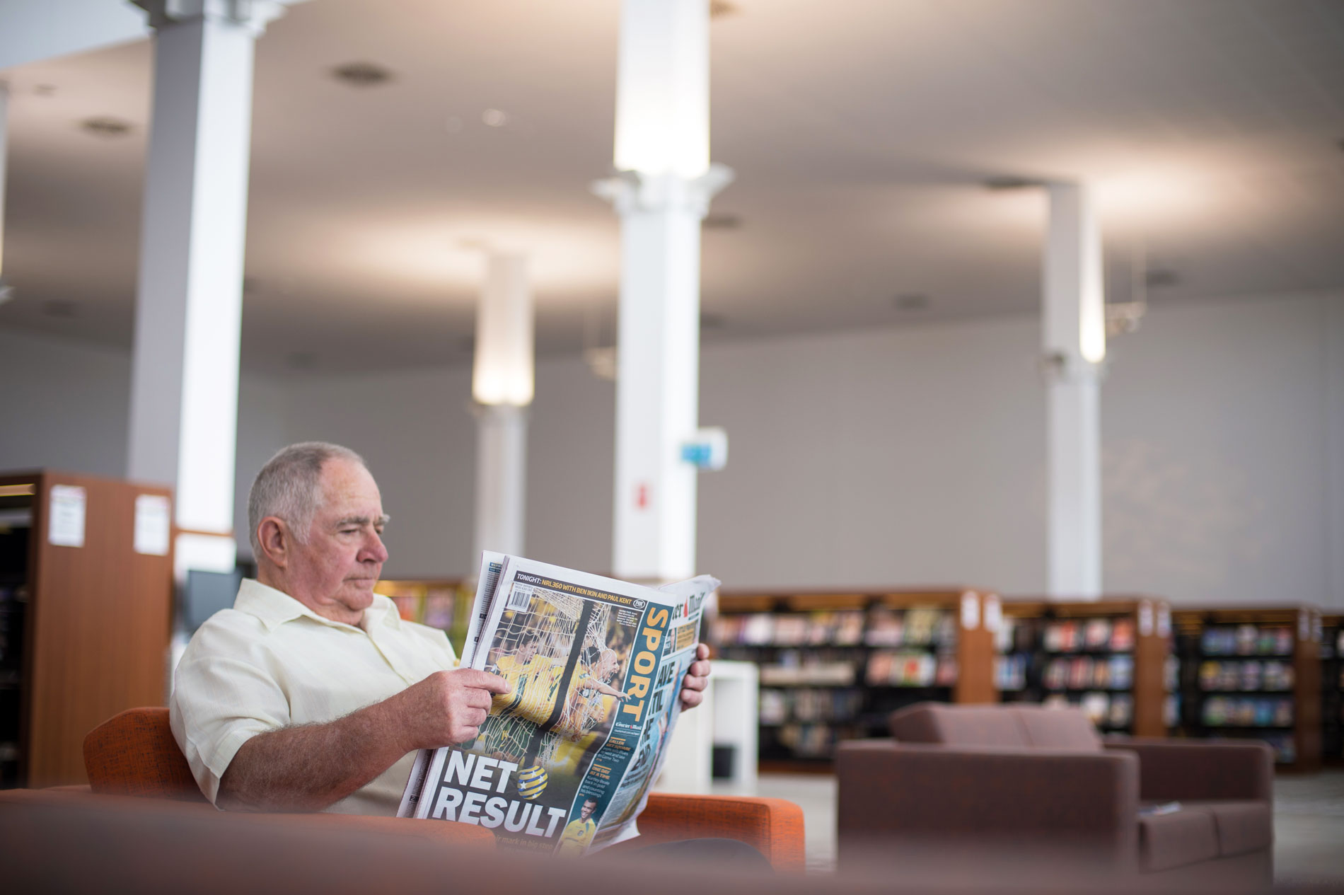 Man reading newspaper in the Caboolture public library