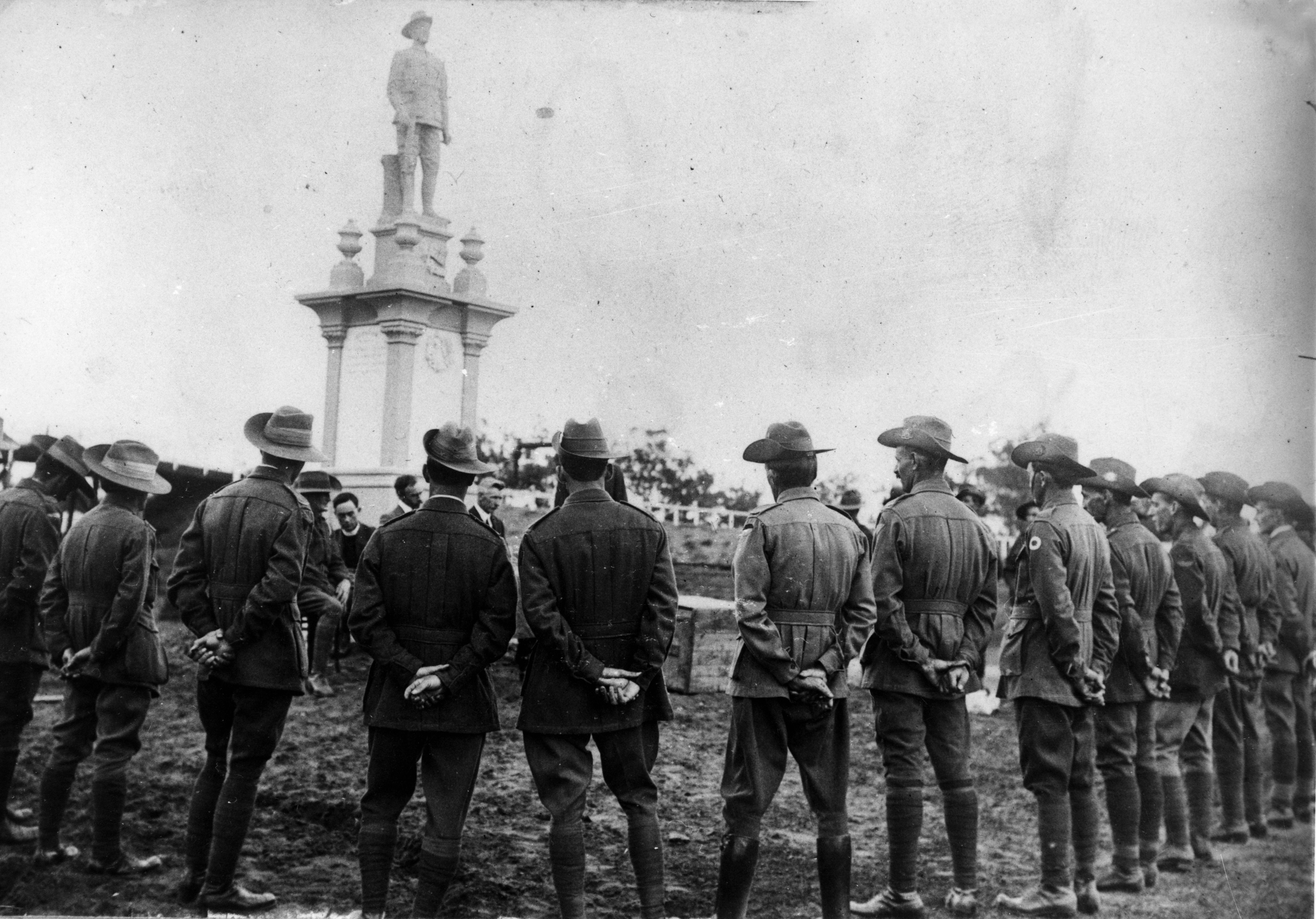 Returned soldiers in uniform surrounding the Digger War Memorial
