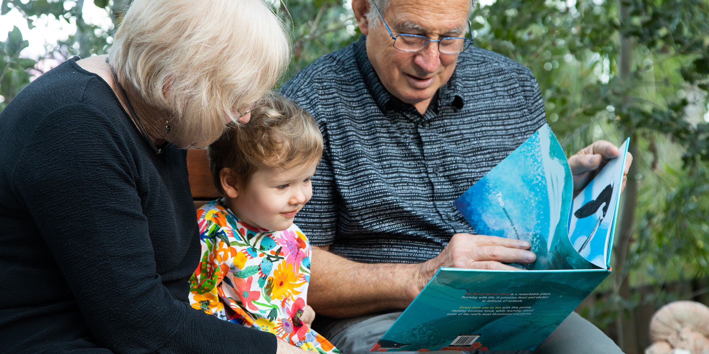 Grandparents reading to young child outside
