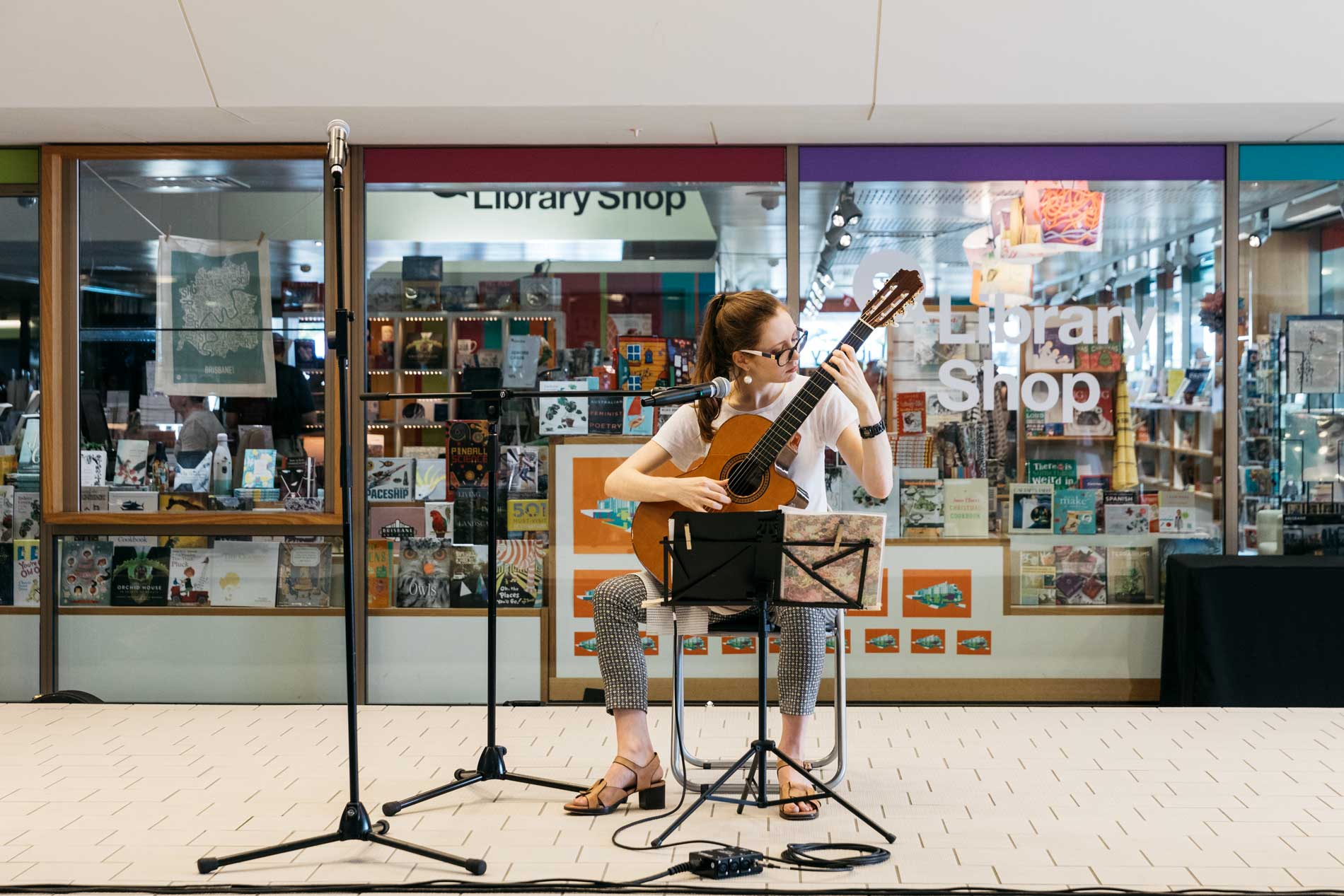 A volunteer musician performing outside the State Library Shop