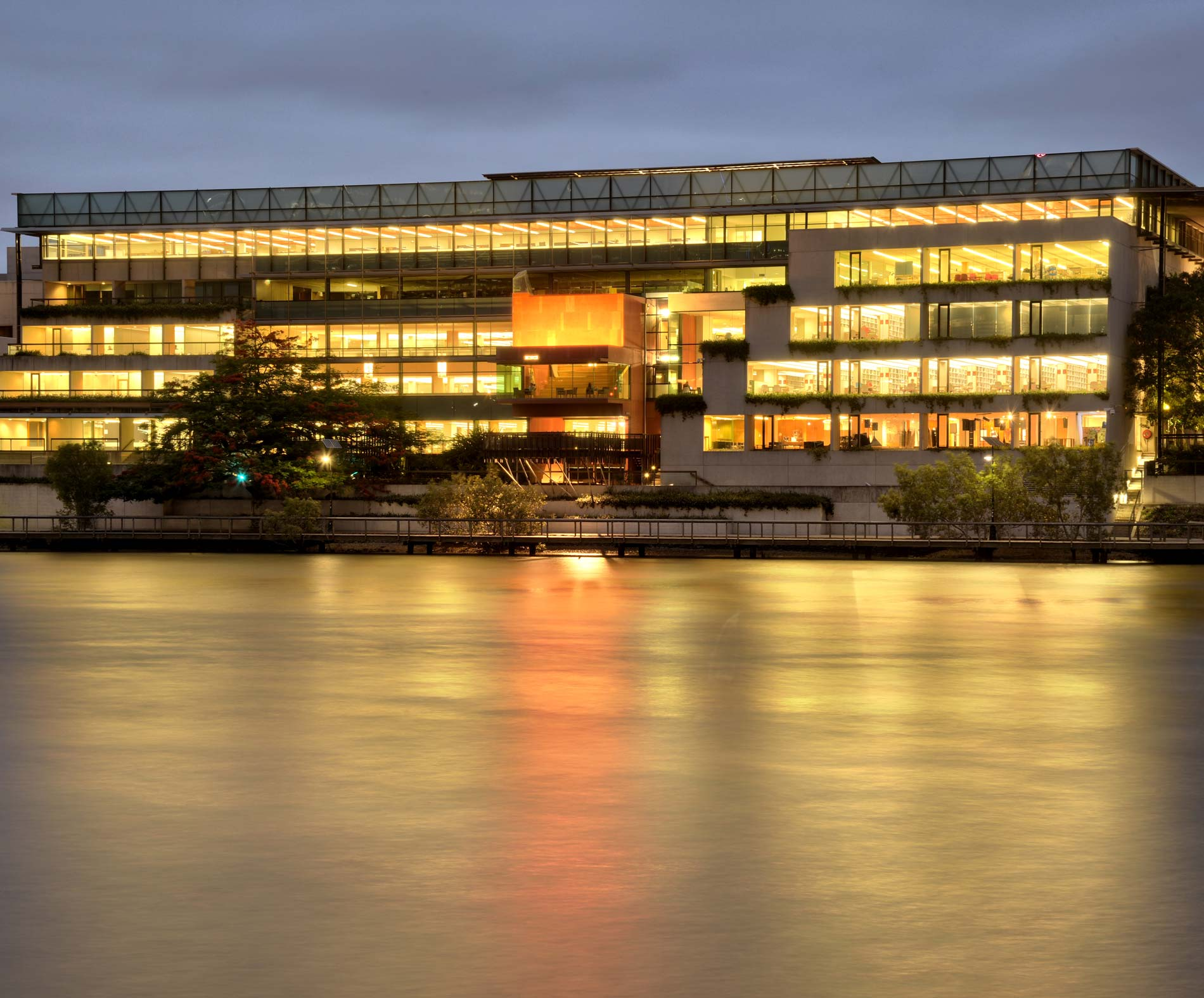 Exterior view of the State Library across the river at evening time