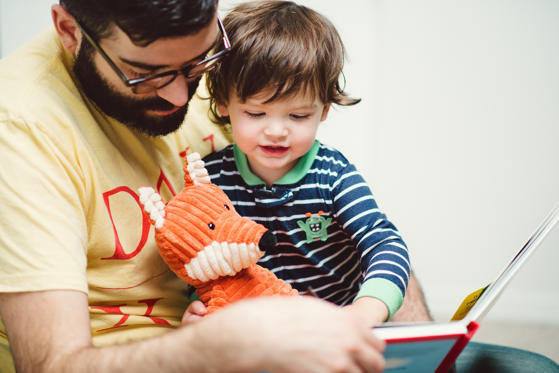 Adult male child and toy fox reading a picture book together