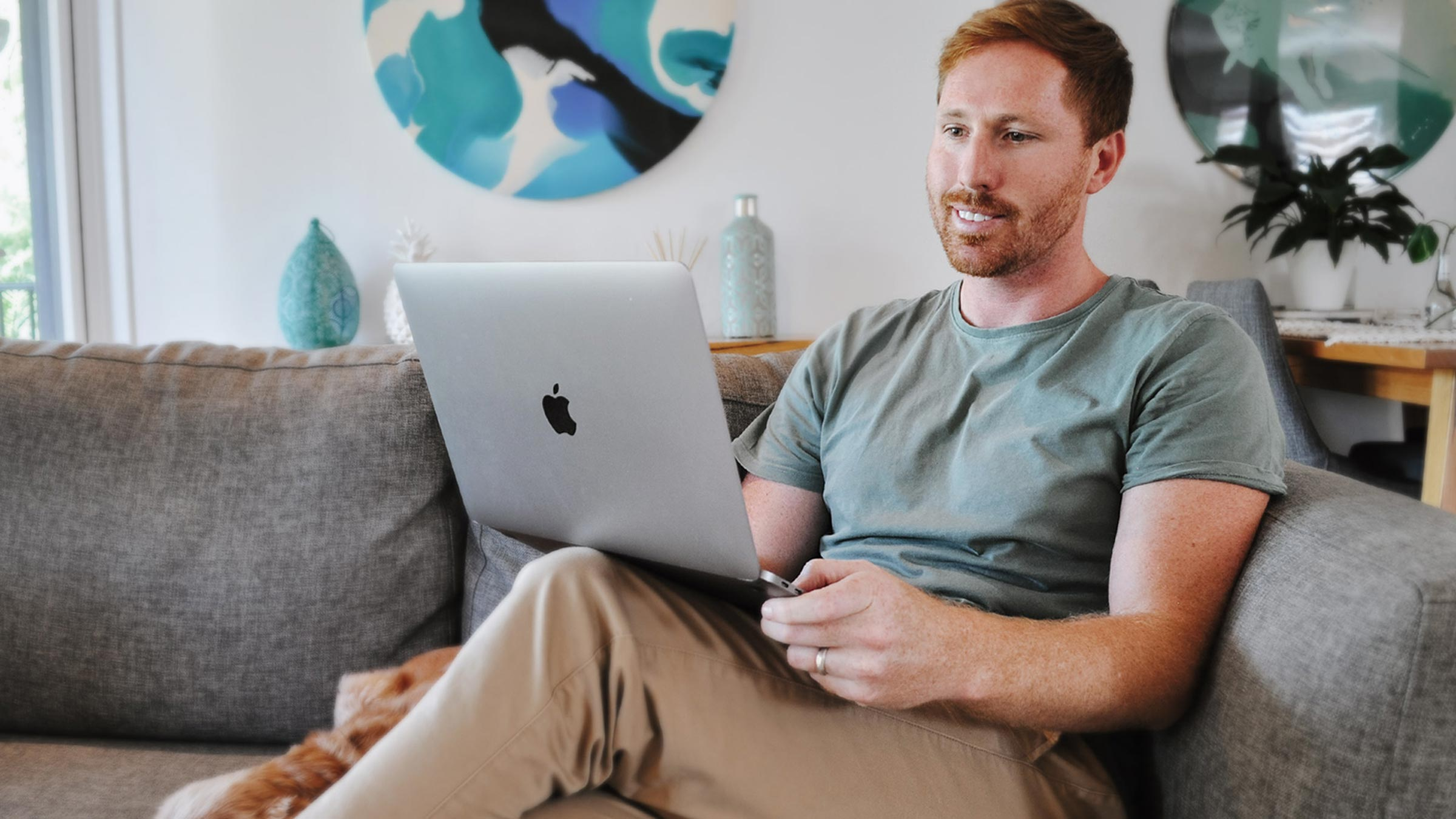 Man sitting on the couch working from home on a laptop