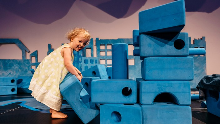 Young girl building with big blue blocks