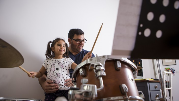 Adult and child playing the drums