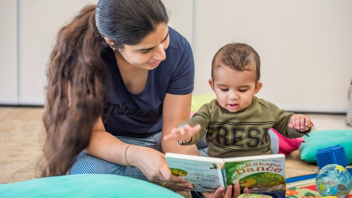 A woman with long dark hair tied in a ponytail is smiling and holding a board book for a little toddler who is looking at the book