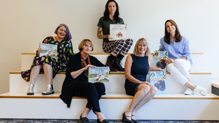 Authors and illustrators holding books they have worked on