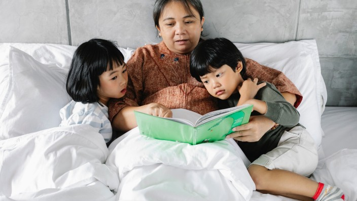 Grandparent reading a bedtime story to two children