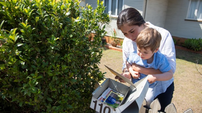 Mother and preschooler checking the mail outside