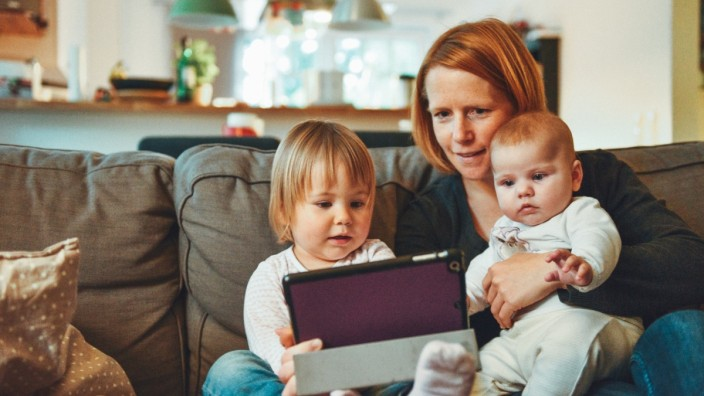 Image of child looking at photos with mum