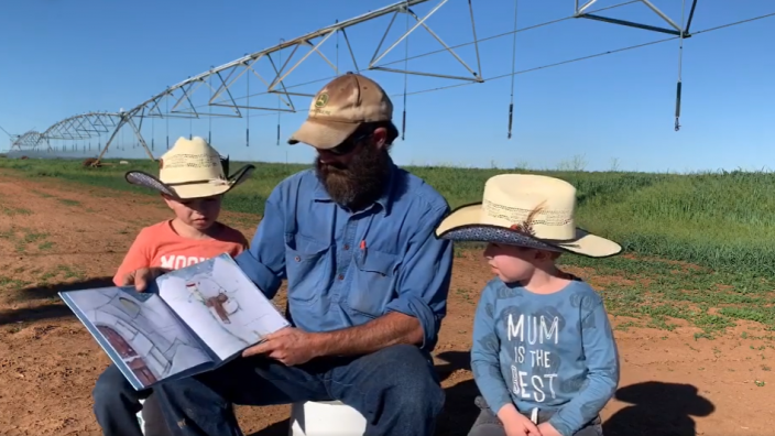 Man and two young sons on a farm reading a story