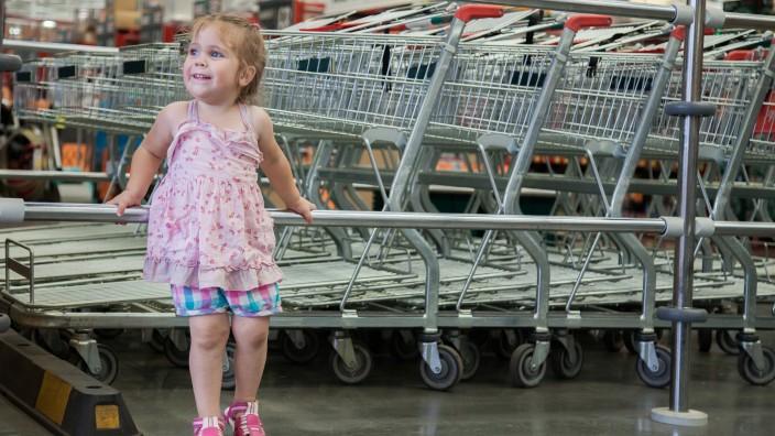 A small child leans against a metal rack where shopping trolleys are lined up behind her She is looking in the distance and looks happy