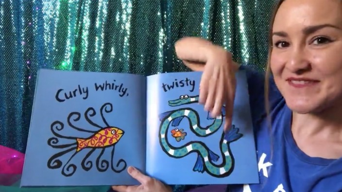 Picture book with fish read by girl in blue tshirt