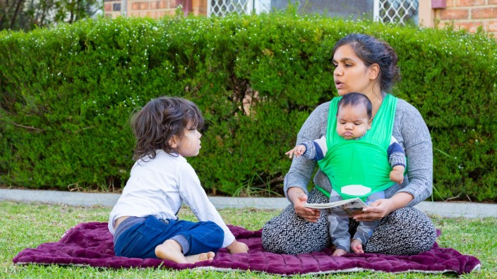 Mother and two children sharing a book outside