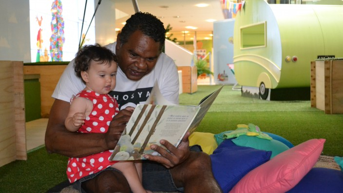 A man is reading to a toddler in a red dress who is sitting on his lap from a picture book They are sitting on brightly coloured cushions