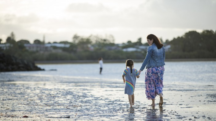 Mother and child walking on beach holding hands