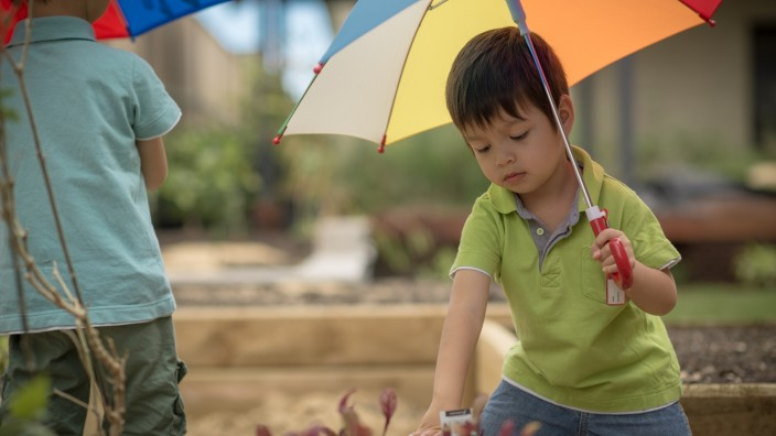 Two children are holding umbrellas One is turned away from the camera The other one is facing forward and looking down at a garden bed