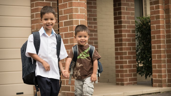 Two boys are holding hands The older boy is dressed in a school uniform and carrying a large backpack They are both smiling
