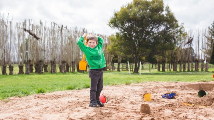 Boy in jumper playing in sandpit