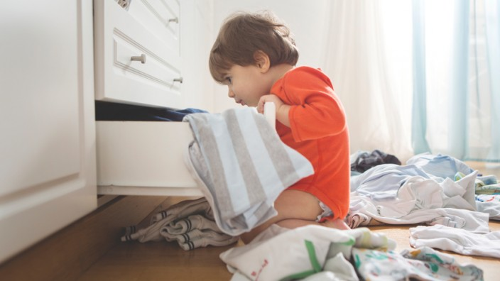 A toddler in an orange jumpsuit is looking into an open clothes drawer There are clothes strewn across the floor