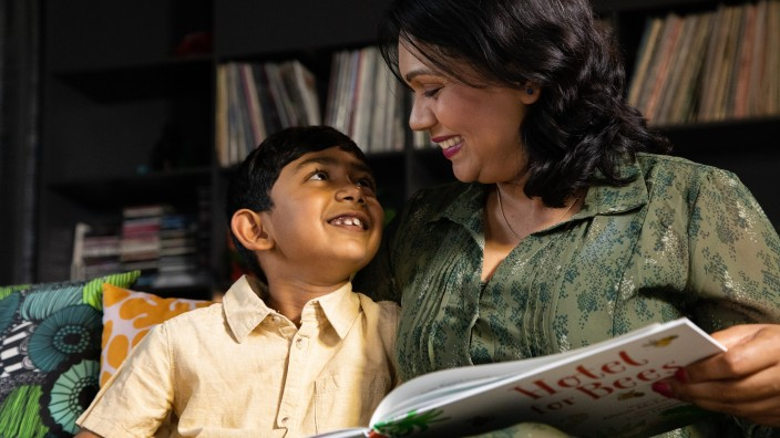 Child smiling at mother who is reading him a story