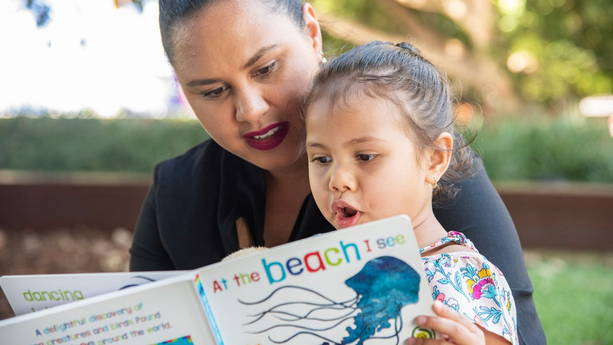 Woman reading a book to a child in an outdoor area
