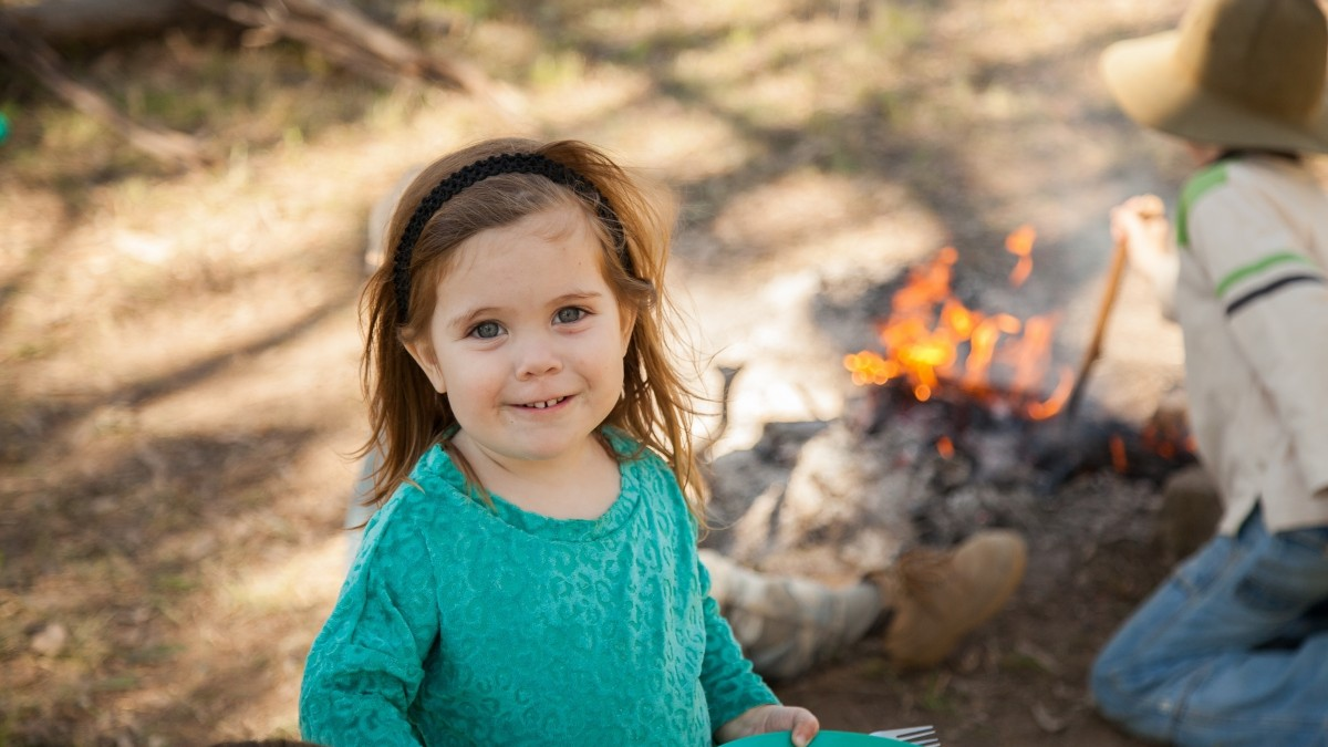 Young girl smiling with a campfire in the background