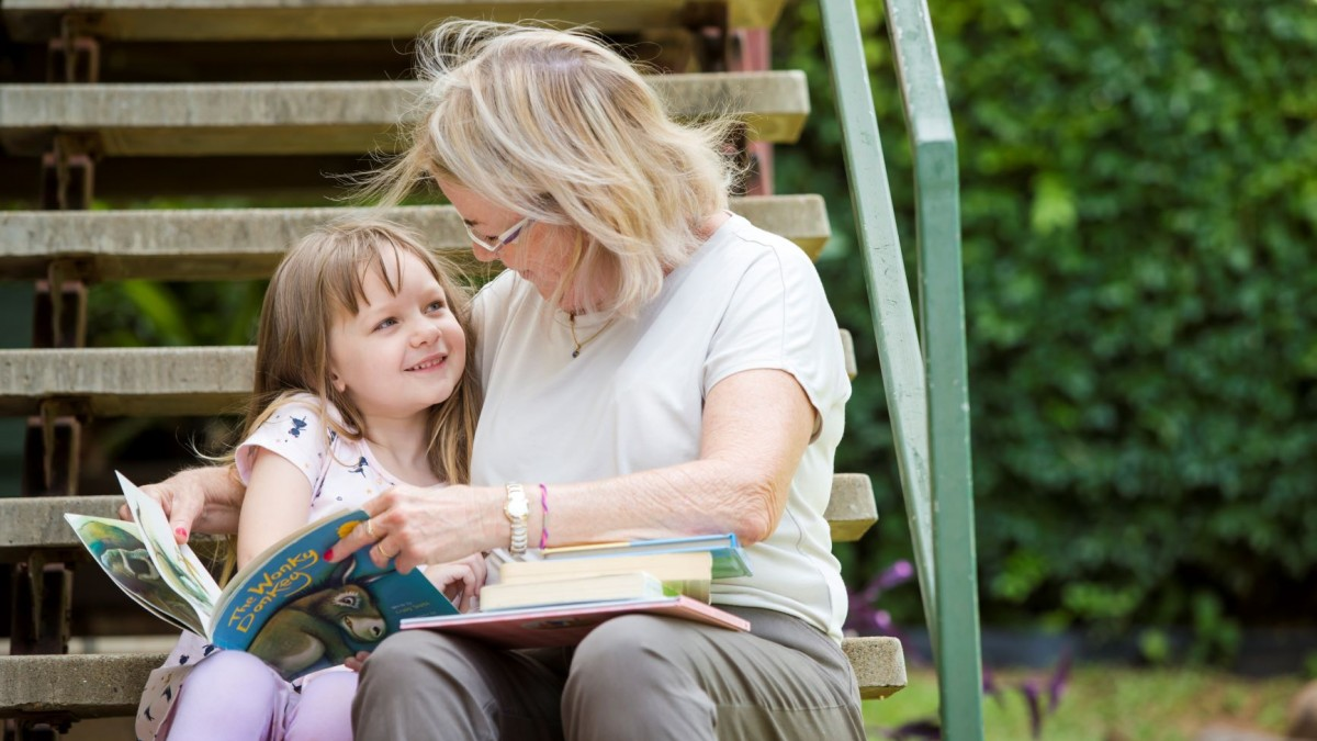 Grandmother and preschooler reading in the garden