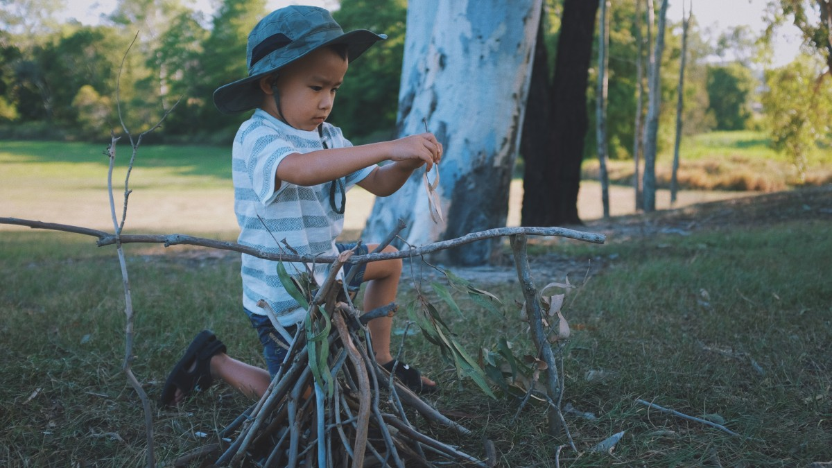 Young boy playing with sticks outside