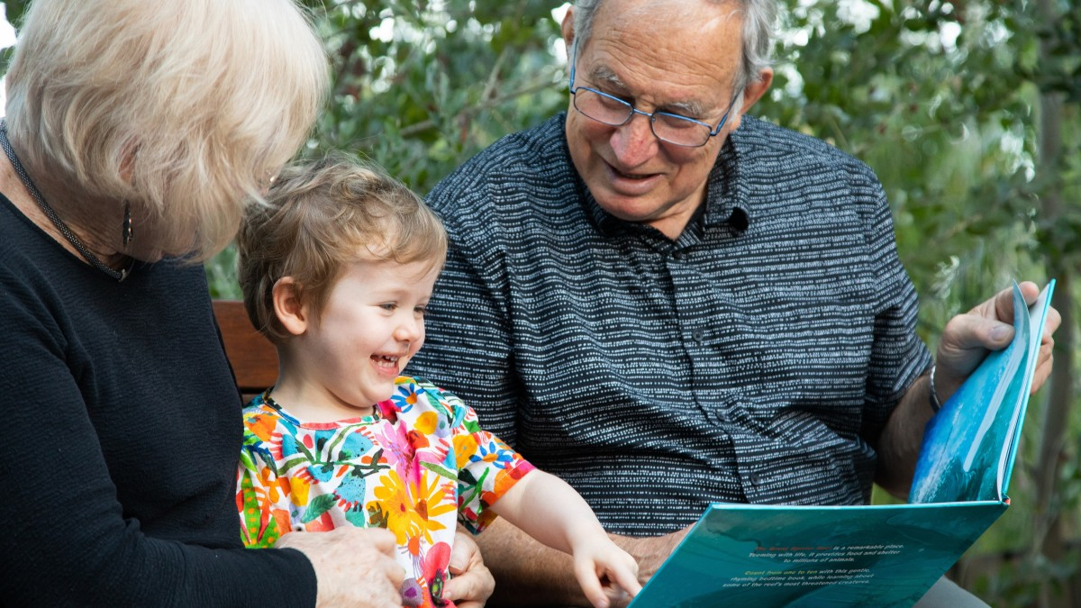 Child smiling as her grandparents read her a story