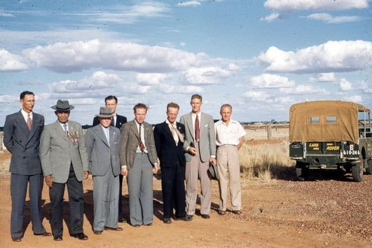 Group of veterans wearing suits and medals standing outside in Boulia near a Landrover in 1954