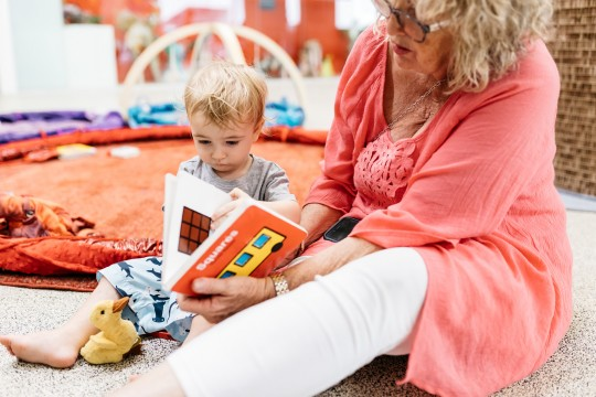 A toddler and their carer reading a book in The Corner