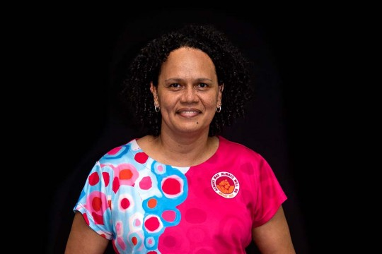 woman smiling at the camera wearing a pink Indigenous shirt