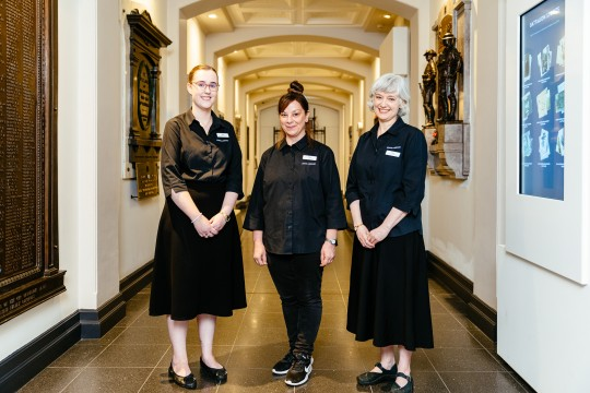 Three staff members at Anzac Square Memorial Galleries standing at the entrance to the World War I crypt