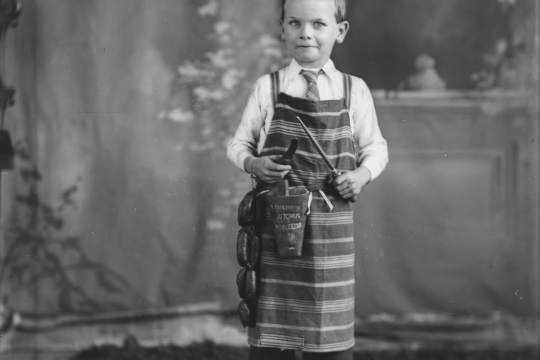 A black and white photograph of a young boy wearing a butchers apron and holding a string of sausages