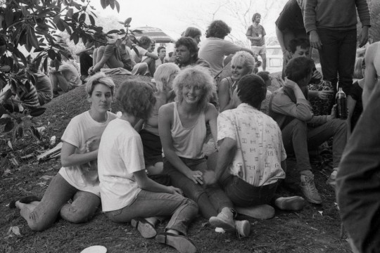 People attending 4ZZZ market day 1982 relaxing on a hill
