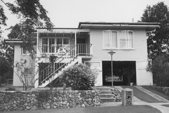 A black and white photograph of a double story house with a stone wall