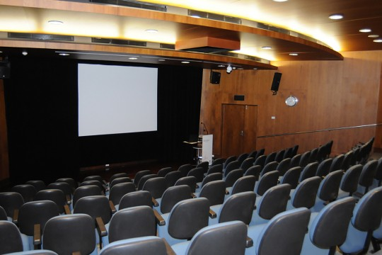 An empty auditorium with large screen and podium at front
