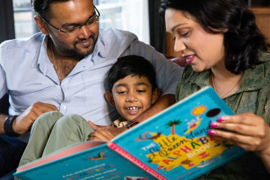 Parents reading book with child