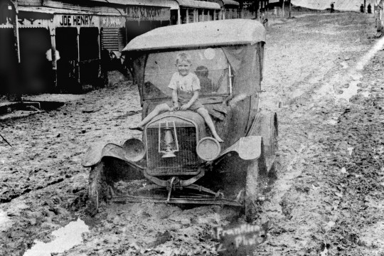 Young boy sitting on the bonnet of an early motor vehicle submerged in mud in Rankin Street Innisfail in 1925 The street is covered in mud and water from the flood which hit the town in March 1925 The car is a Ford Model T between 1917-1927
