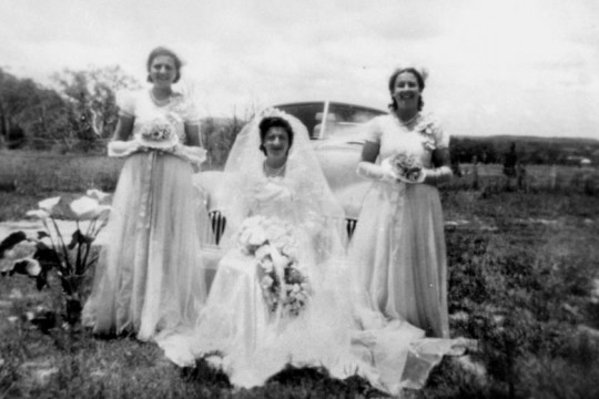 Bride and bridesmaids standing in front of a Holden ca1951 Photographer Unknown John Oxley Library SLQ Negative no 97163