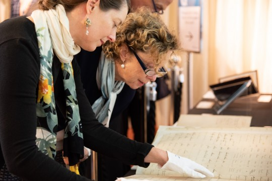 Two women looking at the Synagogue records