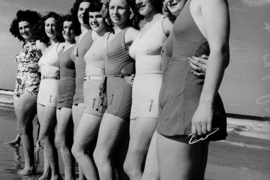 Black and white photo of nine women in bathing costumes standing in line at the waters edge in 1939