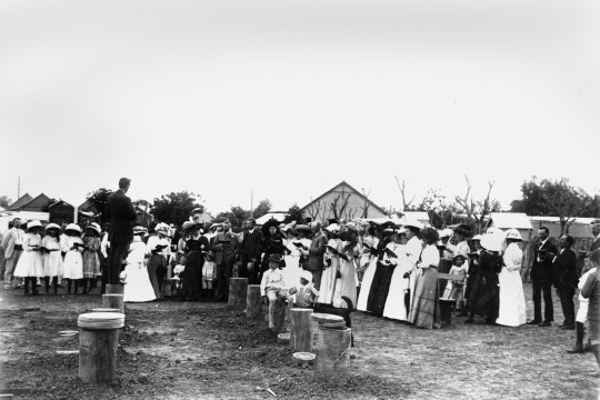 Black and white photo of a gathering of people around the stumps of a building
